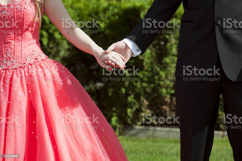 Girl dressed in red for prom holding hands with date stock photo