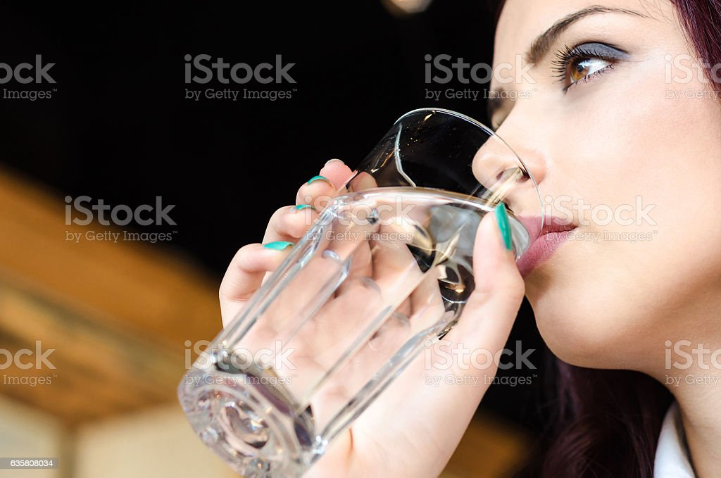Girl drinking a glass of water in a coffee shop stock photo