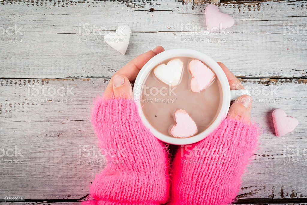 Girl drinking hot chocolate with marshmallows's hearts stock photo