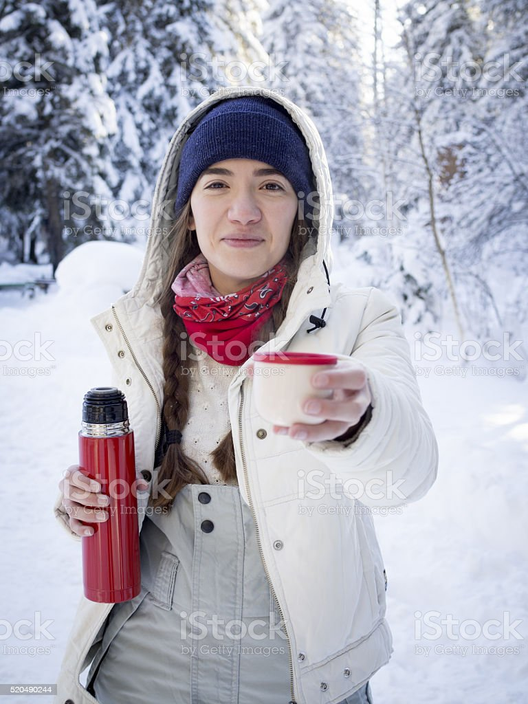 Girl drinking tea from a thermos on a winter mountain. stock photo