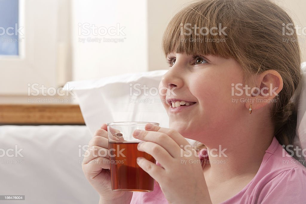 Girl drinking tea while sitting in bed. Indoors. Close-up. royalty-free stock photo