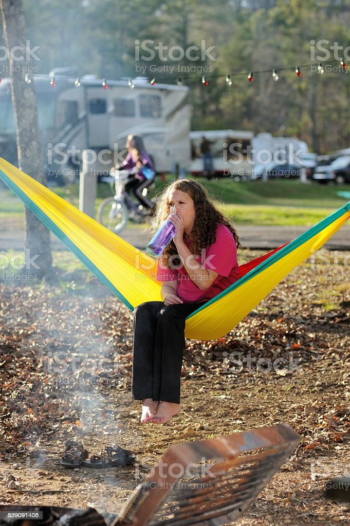 Girl drinking water bottle in hammock at campground stock photo