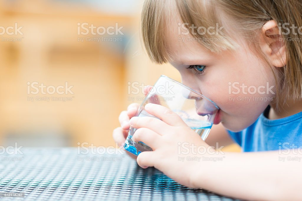 Girl drinking water outdoors stock photo