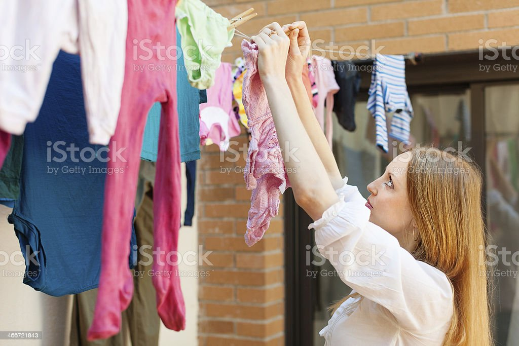 girl drying clothes  after laundry stock photo