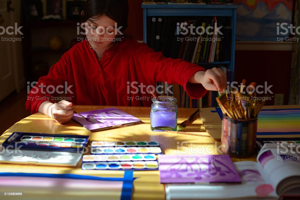 Girl during an art lesson, painting rainbows in the sun stock photo