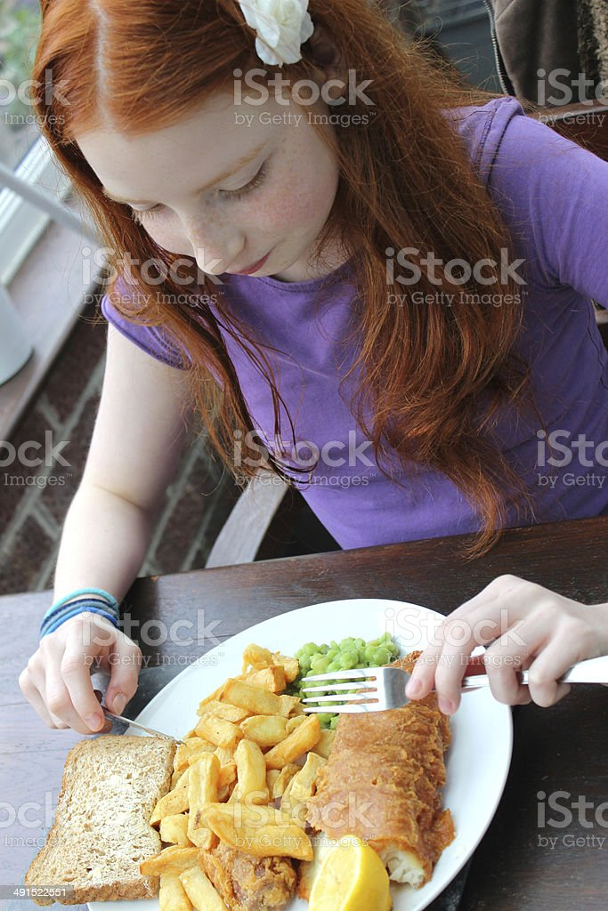 Girl eating a plate of fish and chips, mushy peas stock photo