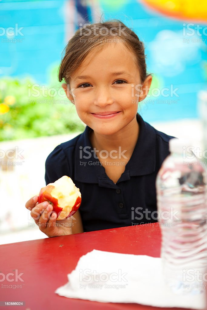 A girl eating an apple during school lunch break royalty-free stock photo