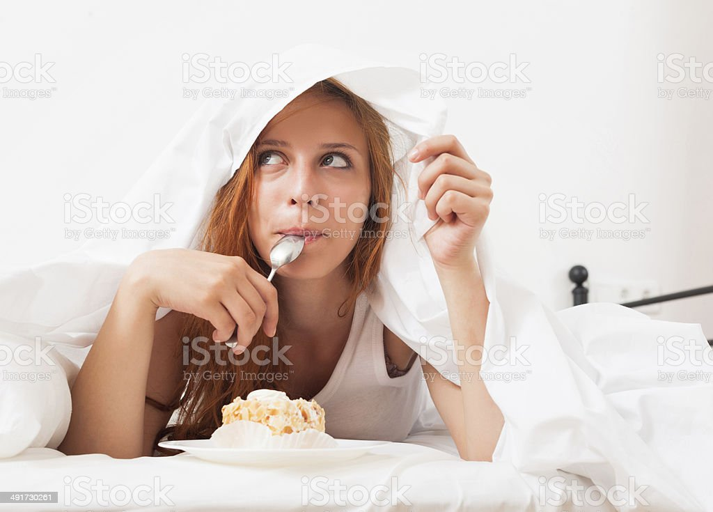 girl eating biscuit in her bed stock photo
