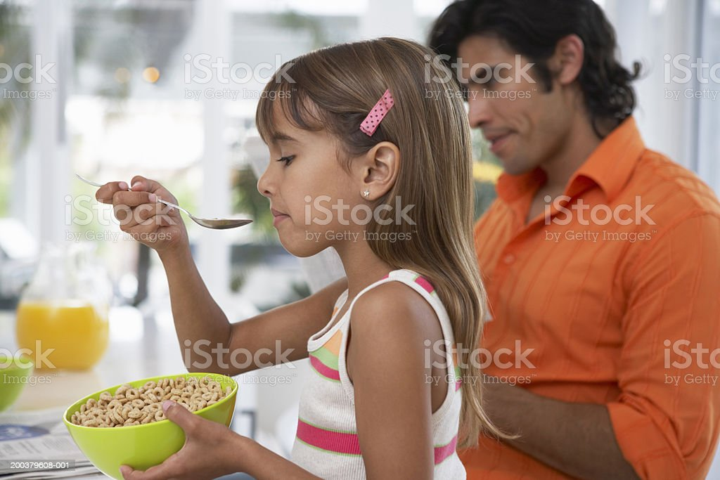 Girl (7-9) eating breakfast cereal sitting with father (focus on girl) royalty-free stock photo
