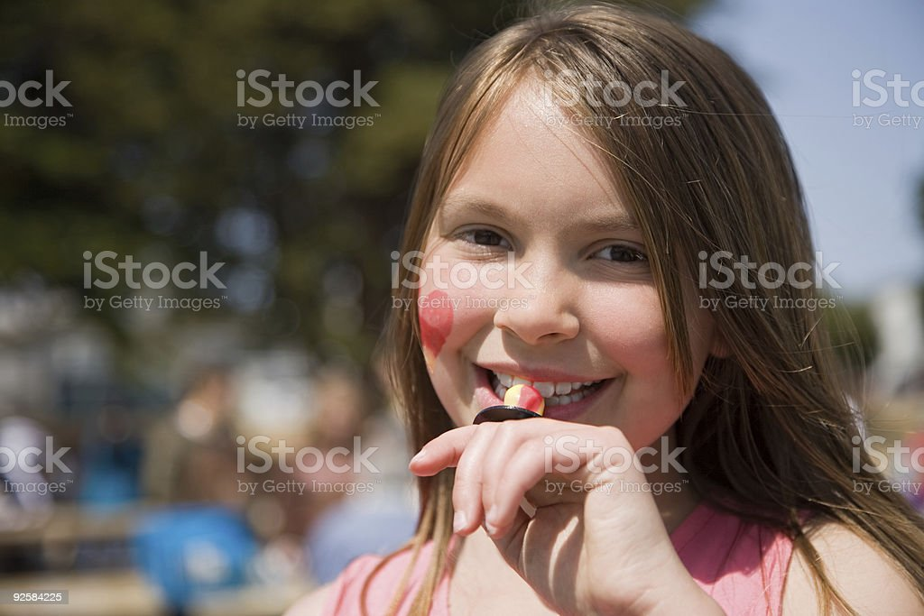 Girl eating candy at festival royalty-free stock photo