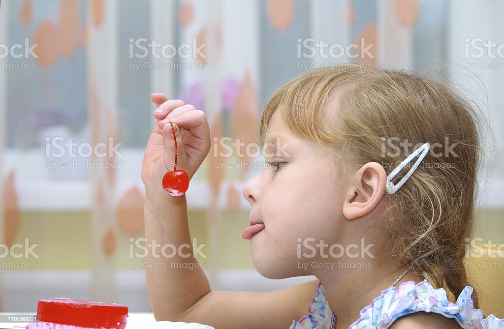 Girl eating dessert with cherry stock photo
