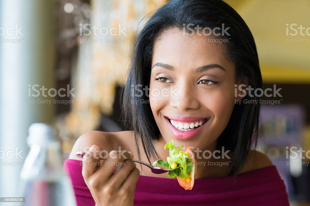 Girl eating fresh salad stock photo