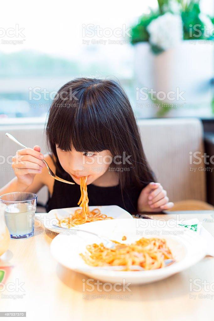 girl eating spaghetti stock photo