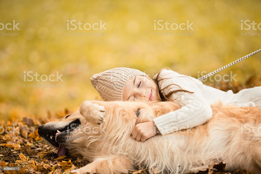 Girl embracing dog in the park stock photo