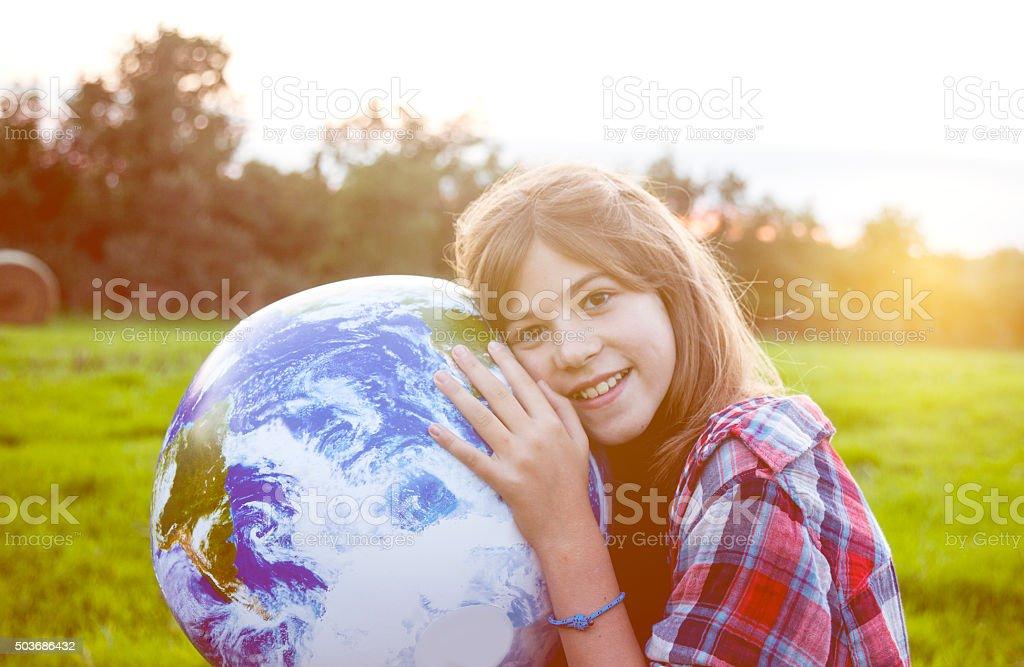 Girl embracing globe stock photo