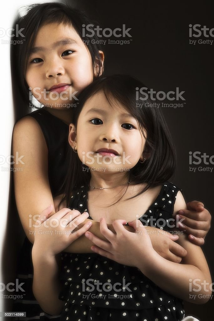 Girl embracing her little sister. royalty-free stock photo