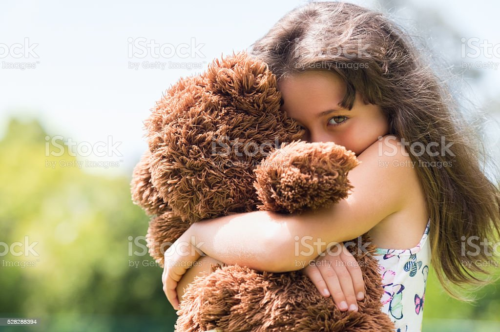 Girl embracing teddy bear stock photo