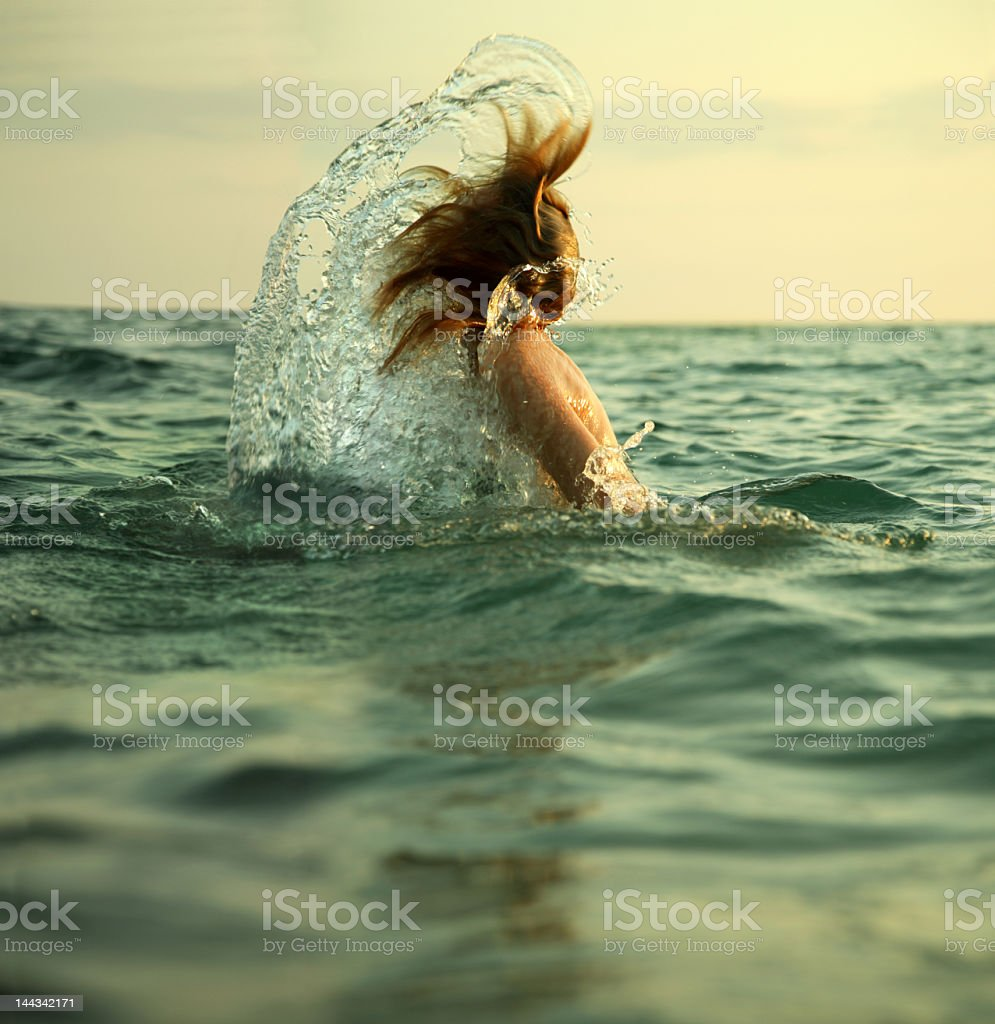 Girl emerges from sea with hair whipping back royalty-free stock photo