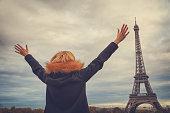 Girl enjoying and watching Eiffel tower in Paris, France.