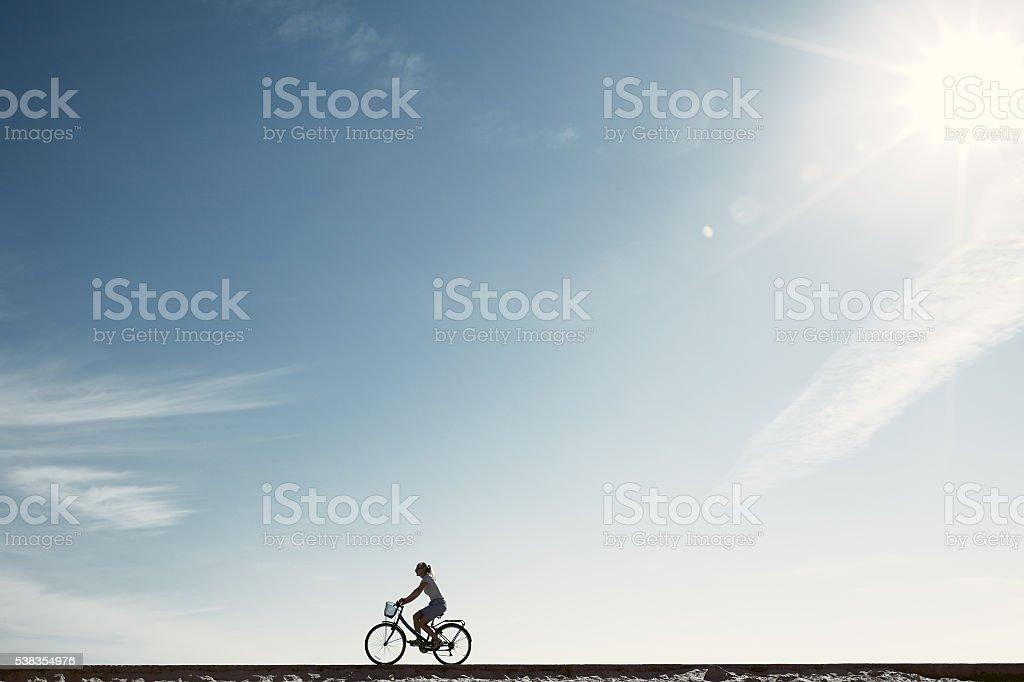 Girl enjoying bike ride silhouette stock photo