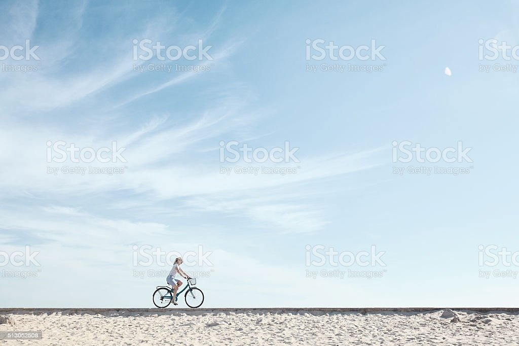 Girl enjoying bike ride under sky stock photo