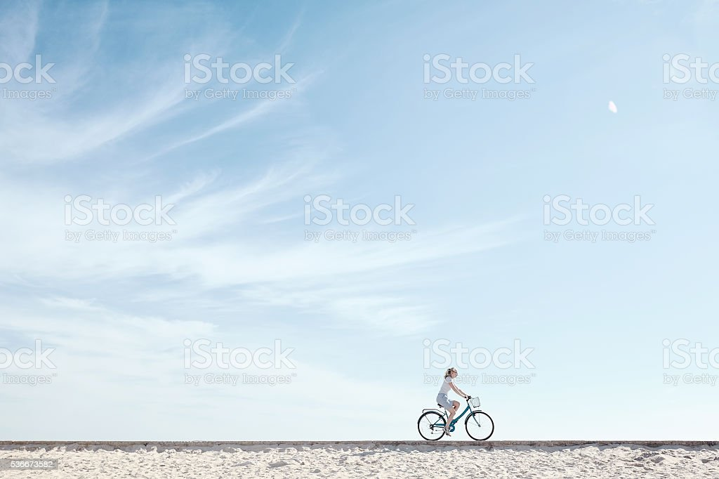 Girl enjoying bike ride under sky royalty-free stock photo