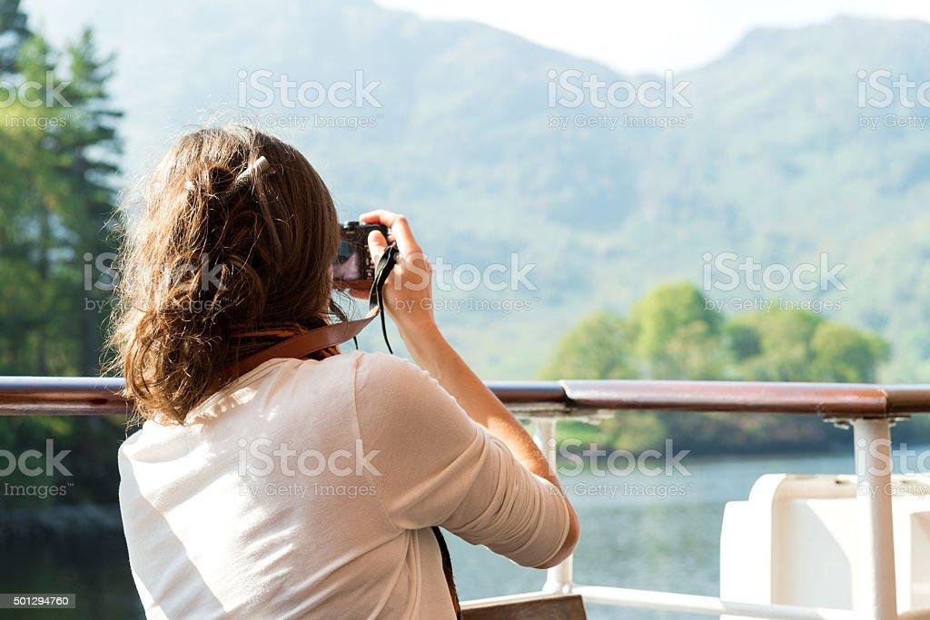 Girl enjoying boat ride, taking photographs, Loch Katrine, Scotland stock photo