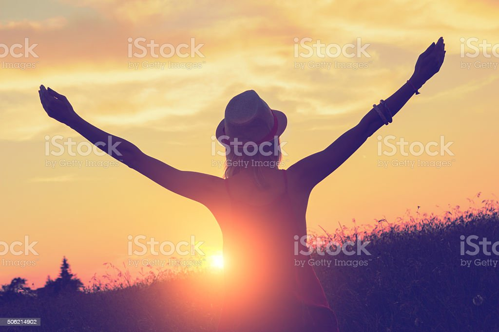 Girl enjoying in a countryside scenic in sunset. stock photo