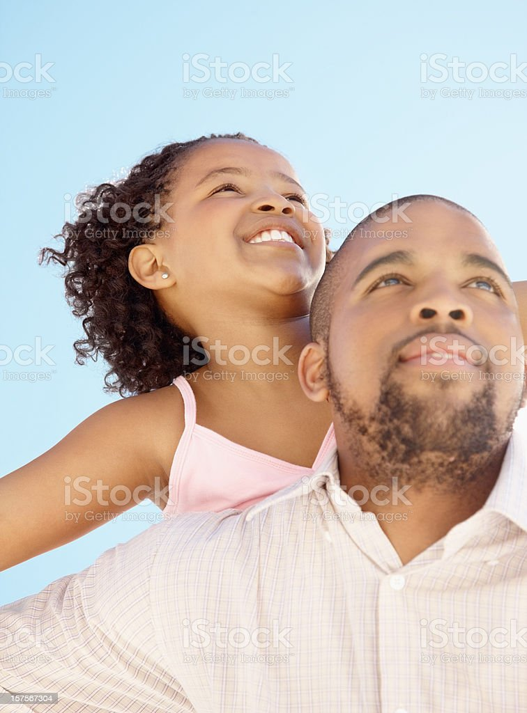 Girl enjoying piggyback ride on father's back royalty-free stock photo