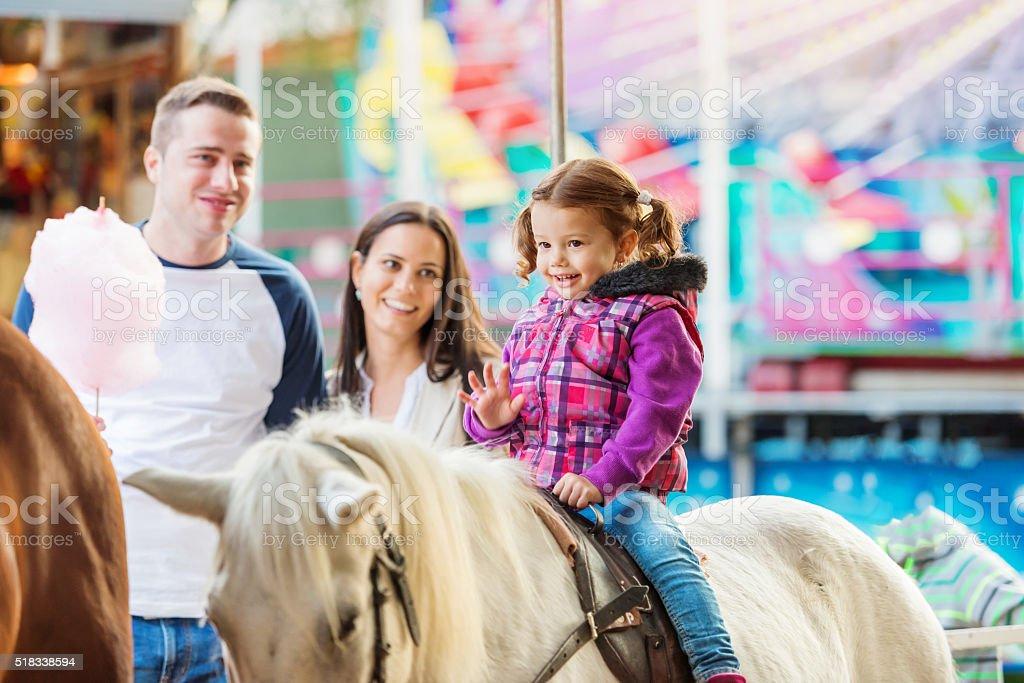 Girl enjoying pony ride, fun fair, parents watching her stock photo