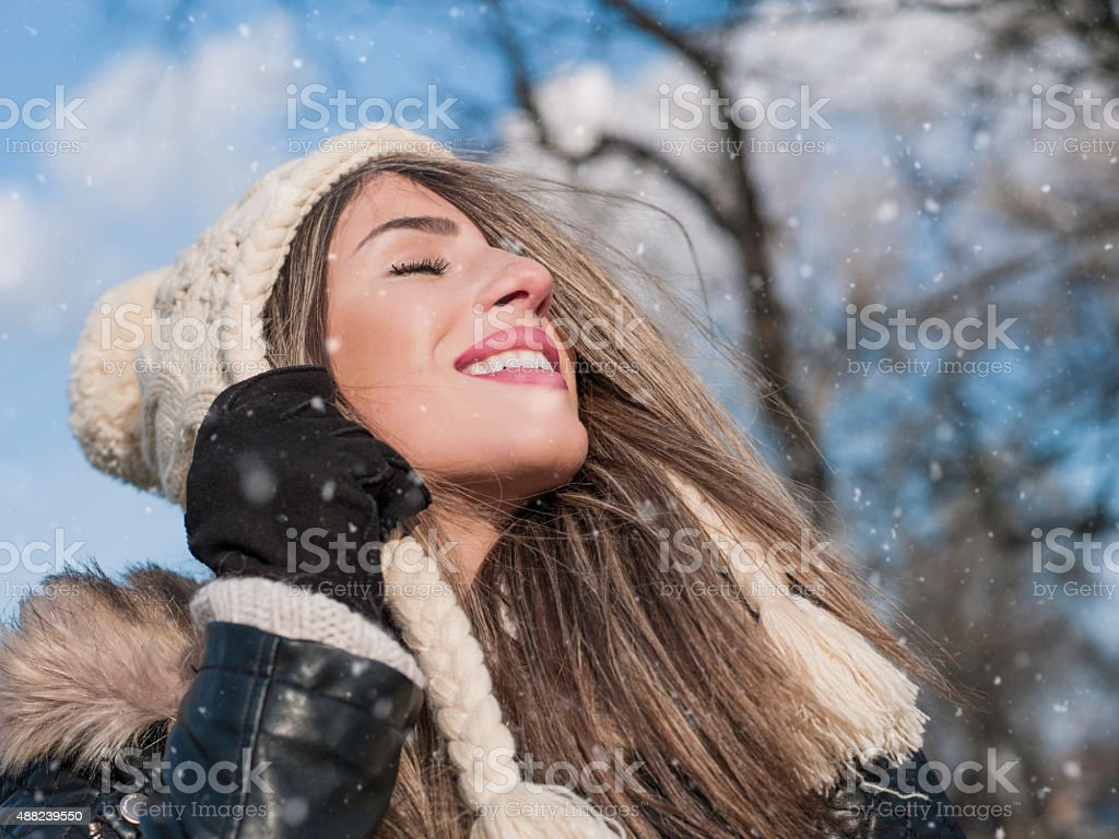 Girl enjoying snow with eyes closed with wool hat stock photo
