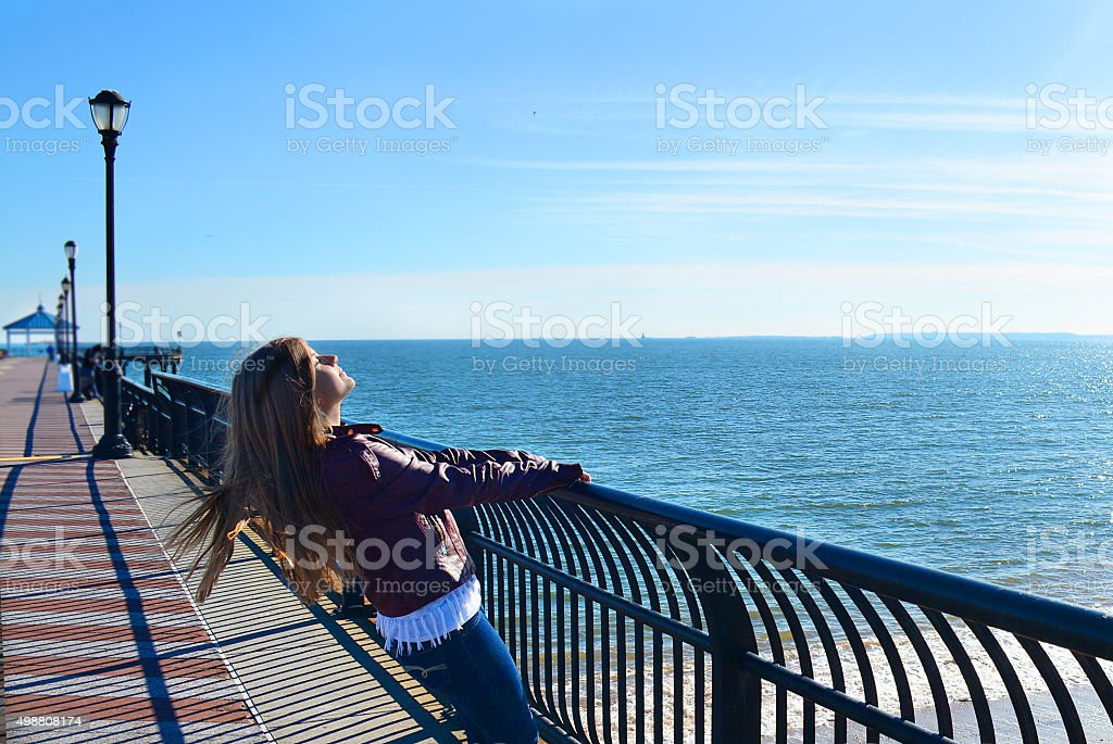 Girl enjoying  sun on the beach. stock photo