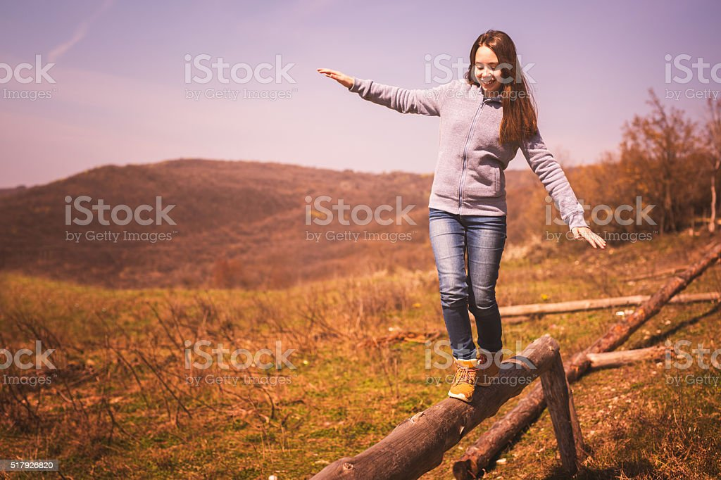 Girl enjoying the nature walking on the balance beam stock photo