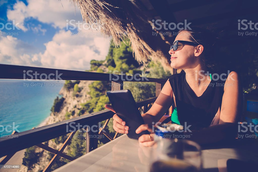 Girl enjoying the sun while surfing on her tablet stock photo
