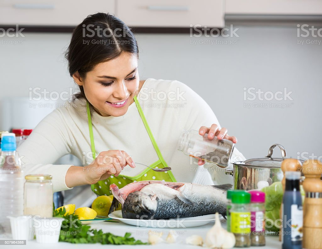 girl eviscerating salmon fish in domestic kitchen stock photo