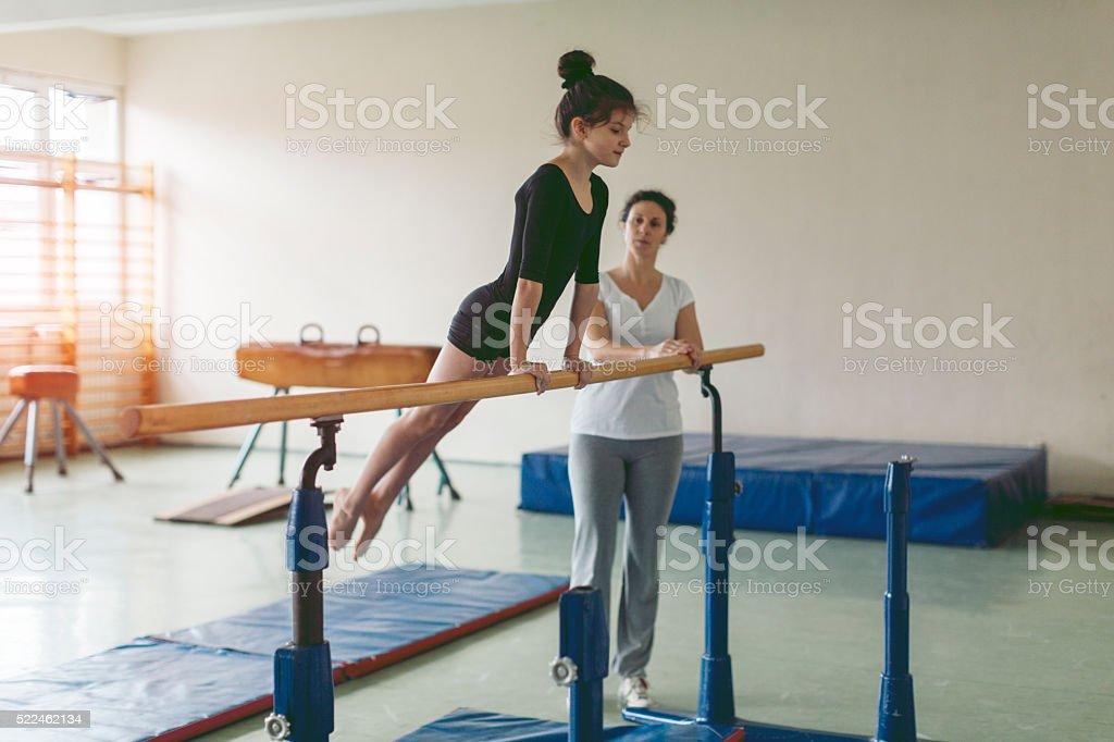 Girl Exercise On Gymnastics Bar. stock photo