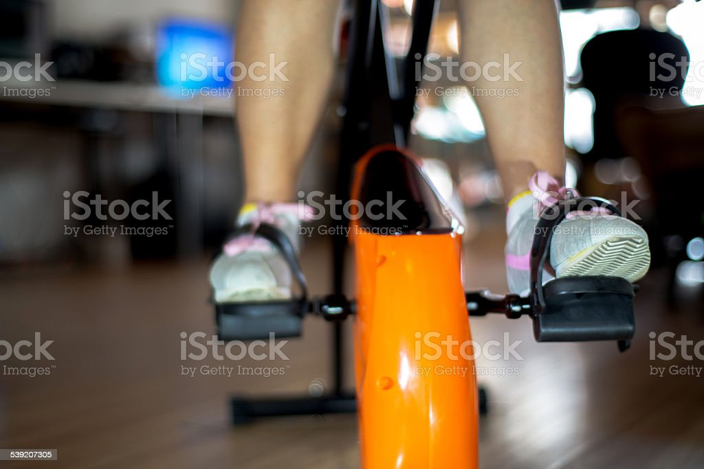 girl exercising fitness bicycle stock photo