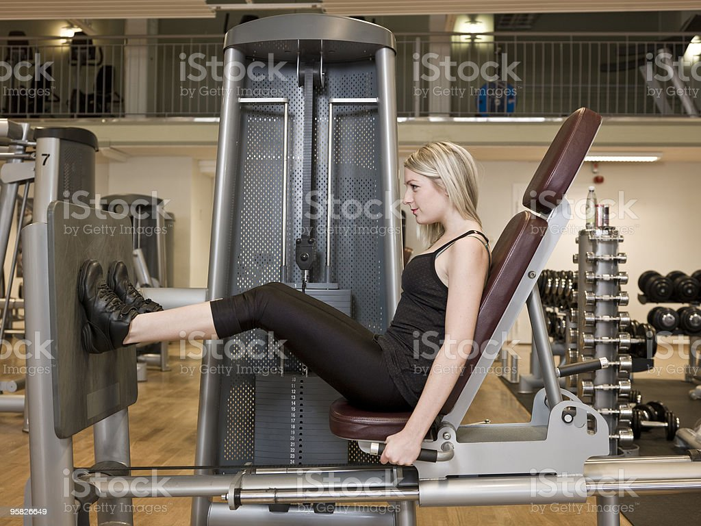 Girl exercising her legs in equipment at the gym royalty-free stock photo
