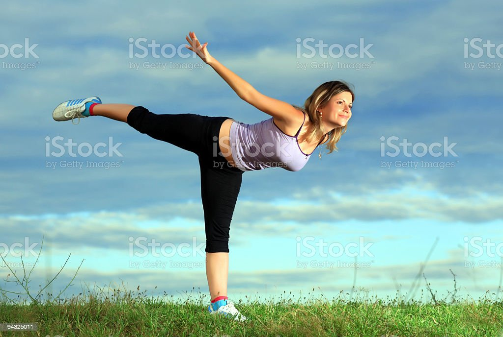 Girl exercising in meadow against blue sky royalty-free stock photo