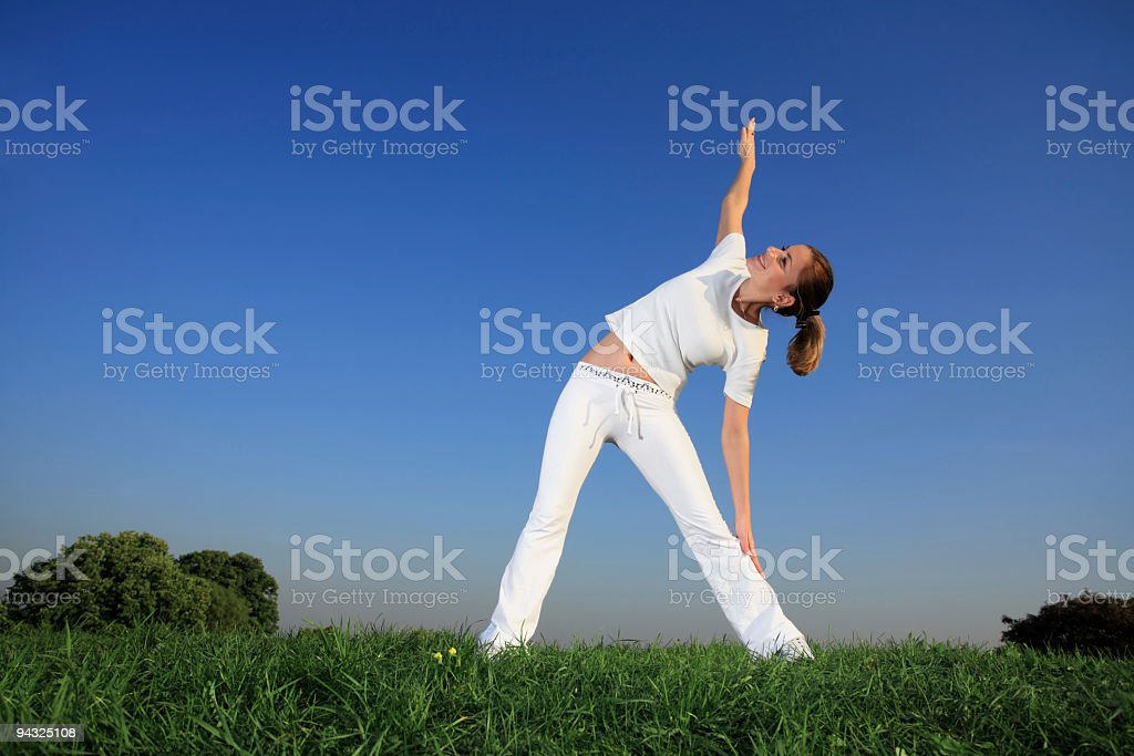 Girl exercising on meadow royalty-free stock photo