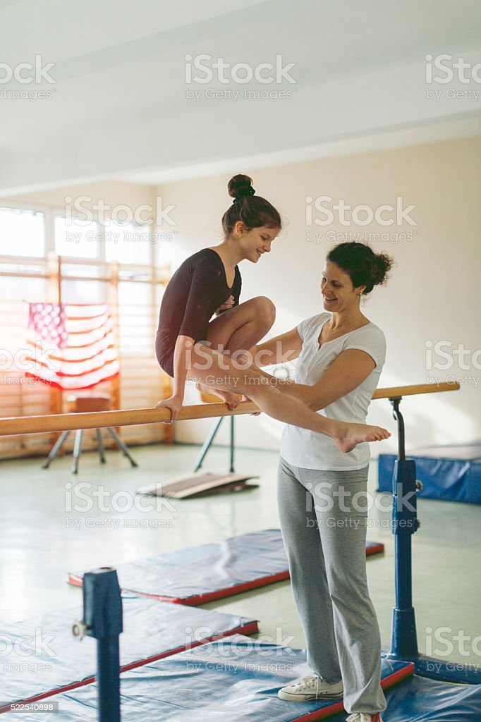 Girl exercising on uneven bars. stock photo