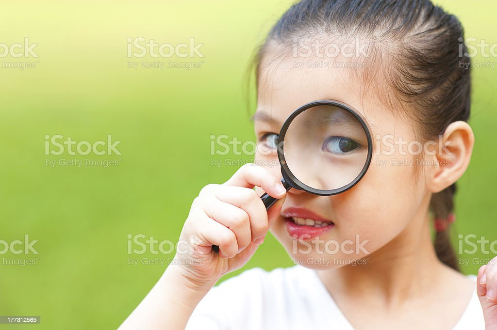 A girl exploring with a magnifying glass stock photo