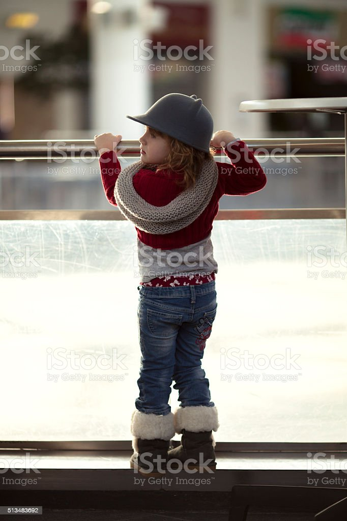 Girl fedora hat and jeans, looking  ice rink stock photo