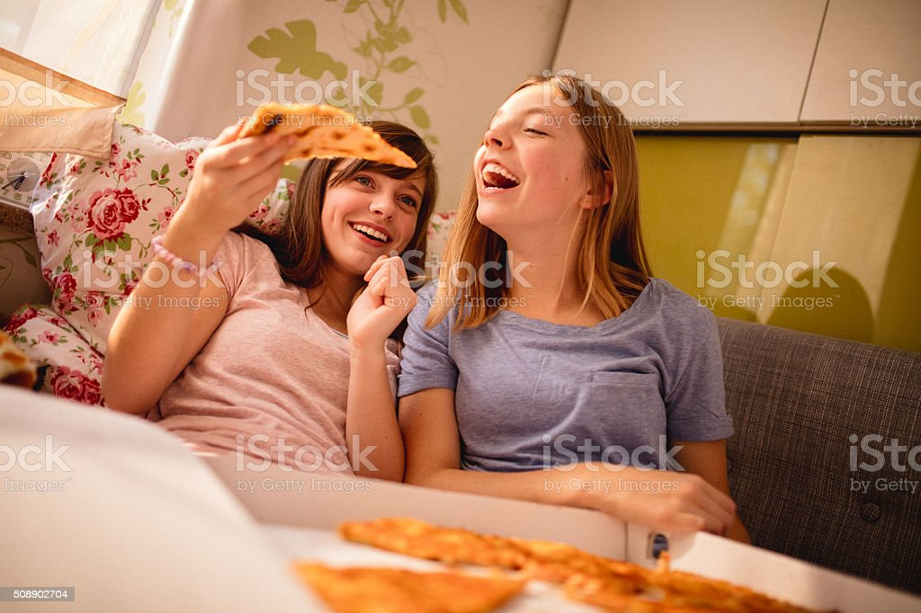 Girl feeding her friend pizza at afternoon pyjama party stock photo