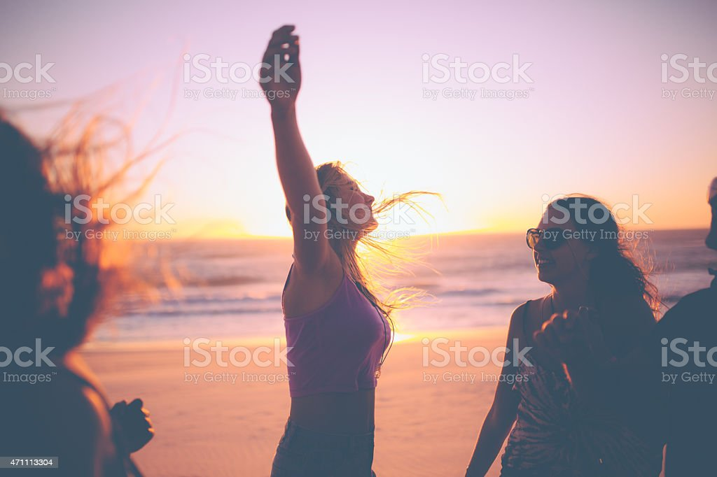 Girl feeling free against a beach sunset with friends stock photo