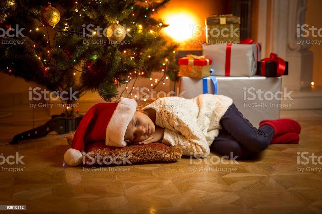 girl fell asleep under Christmas tree while waiting for Santa stock photo