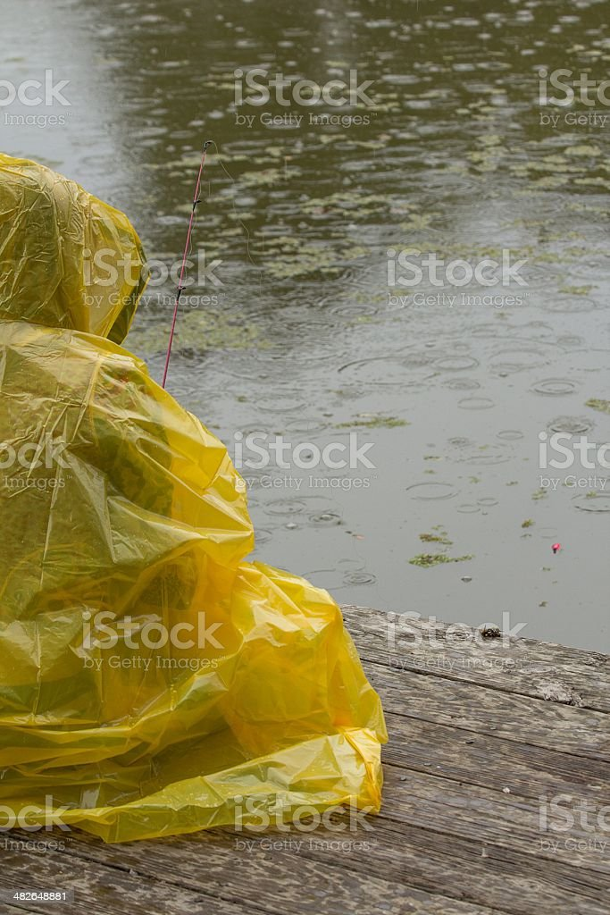 Girl fishing in the rain stock photo