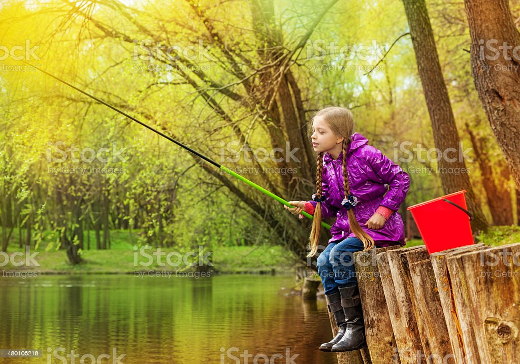 Girl fishing near beautiful pond with fishrod stock photo