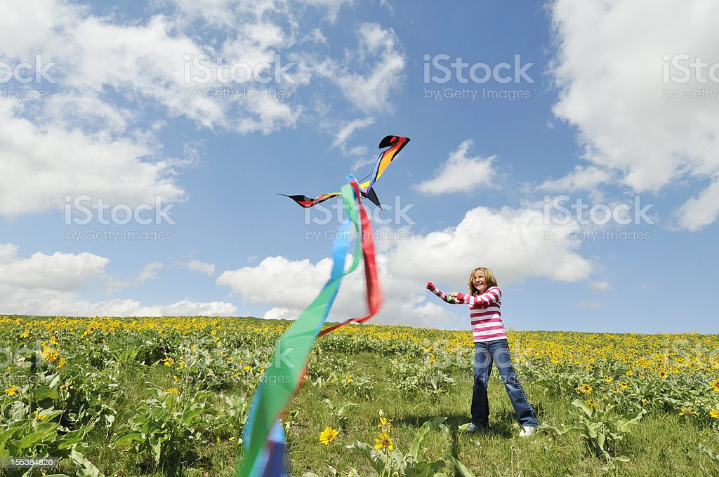 Girl flies kits in flower filled meadow royalty-free stock photo