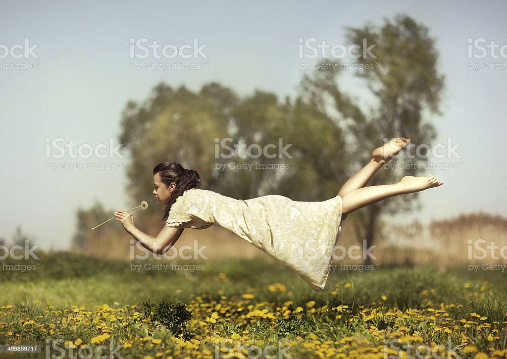 Girl flies over a field. stock photo
